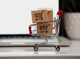 Many paper boxes in a small shopping cart on a laptop keyboard. Concepts about online shopping that consumers can buy things directly from their home or office just using a few clicks via web browser.