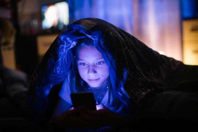 Little girl in bed under a blanket looking at the smartphone at night.